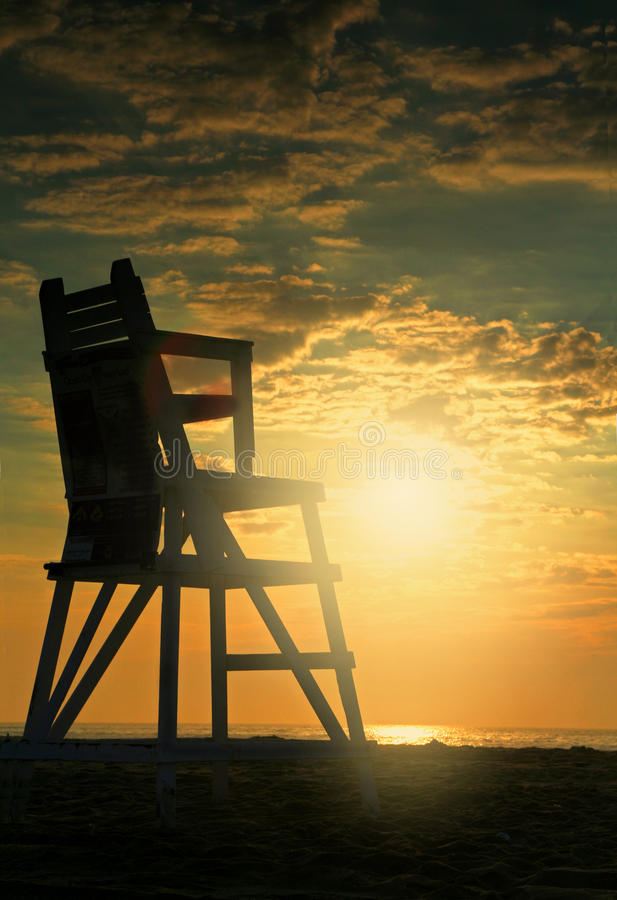 Sunrise on beach with lifeguard seat royalty free stock photo