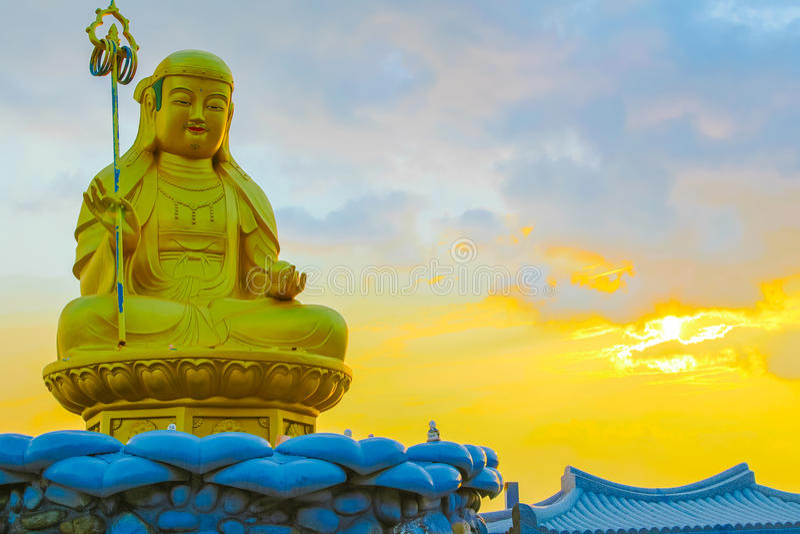 Sunrise behind Buddha statue at Haedong Yonggungsa Temple in Korea royalty free stock images