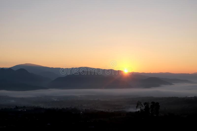 Sunrise behind mountain in the morning with magnificent mist landscape in winter season. stock photos