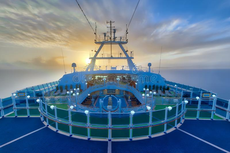 Sunrise on the board. Of the cruise ship . A beautiful scene of the long exposure sunrise on board . Blurred clouds and antenas in motion silky water arond
