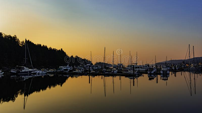Sunrise and boats at Ganges Harbour on Salt Spring Island British Columbia Canada. An orange sunrise and boats reflected at Ganges Harbour on Salt Spring Island stock photo