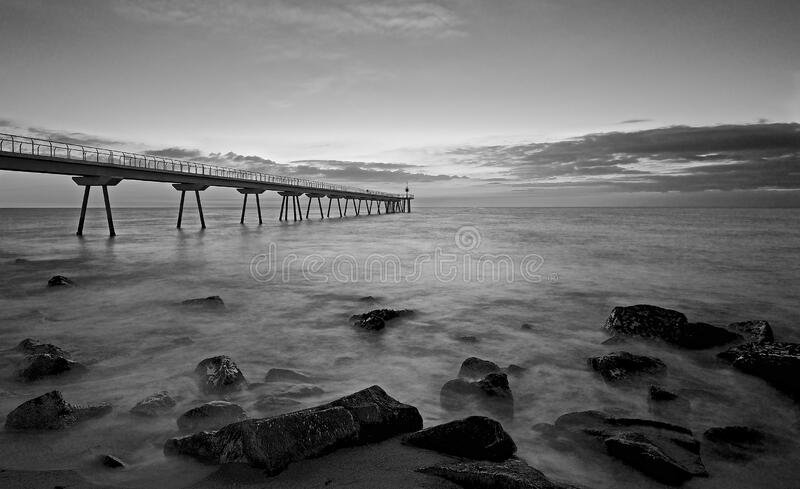 Sunrise on a bridge over the sea. With a lighthouse and some black and white stones stock image