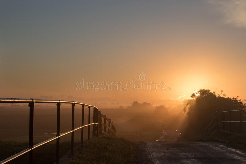 Sunrise from the bridge. View from a bridge looking towards the sunrise with mist in the distance and sun reflecting off metal railings royalty free stock image