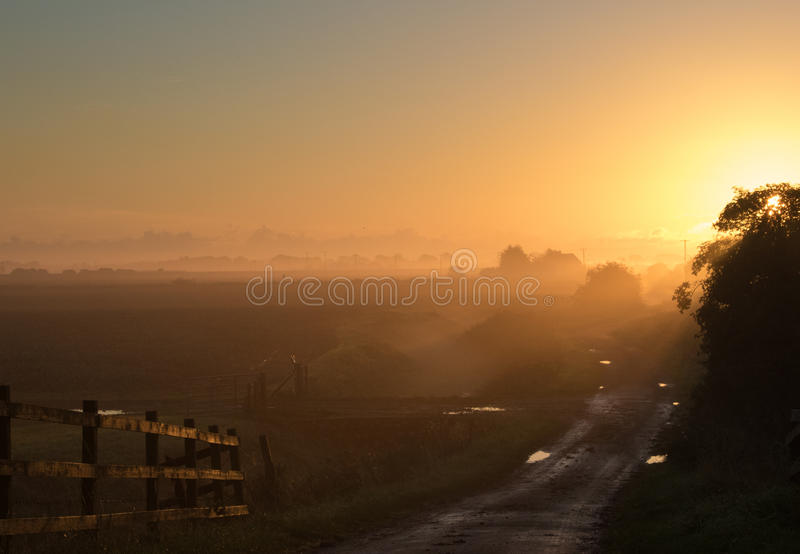 Sunrise from the bridge. View from a bridge looking towards the sunrise with mist in the distance and sun reflecting off a wooden fence stock images