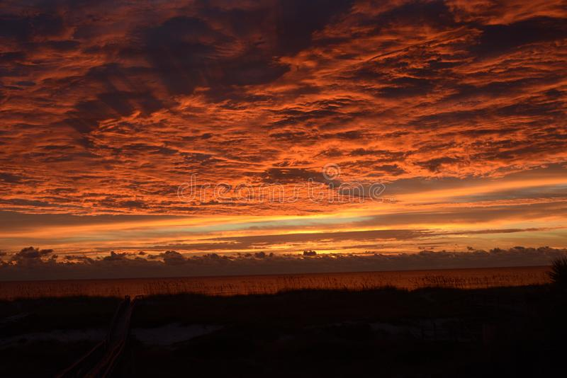Sunrise brings an incredible display of vivid colors over the island waters below stock images