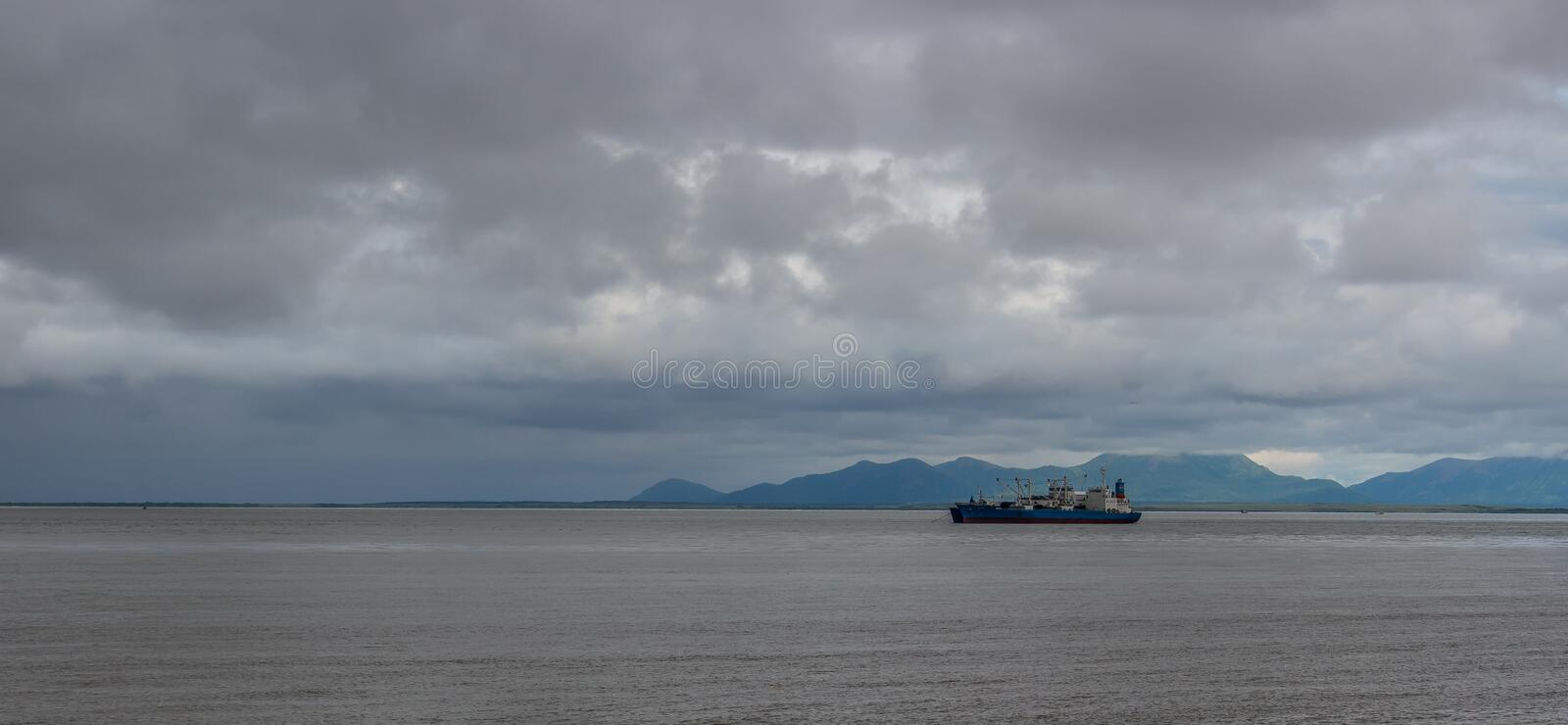 Sunrise on Bristol Bay from Ekuk Alaska. Salmon tender anchored waiting for the start of the season on a cloudy overcast day royalty free stock photos