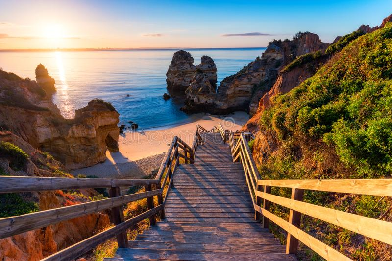 Sunrise at Camilo beach in Lagos, Algarve, Portugal. Wooden footbridge to the beach Praia do Camilo, Portugal. Picturesque view of royalty free stock image