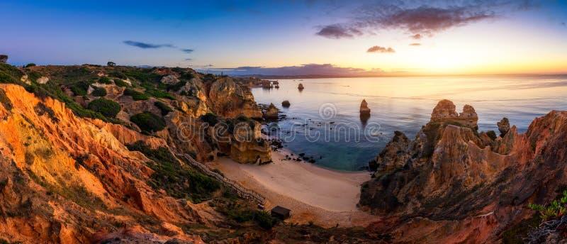 Sunrise at Camilo beach in Lagos, Algarve, Portugal. Wooden footbridge to the beach Praia do Camilo, Portugal. Picturesque view of stock images