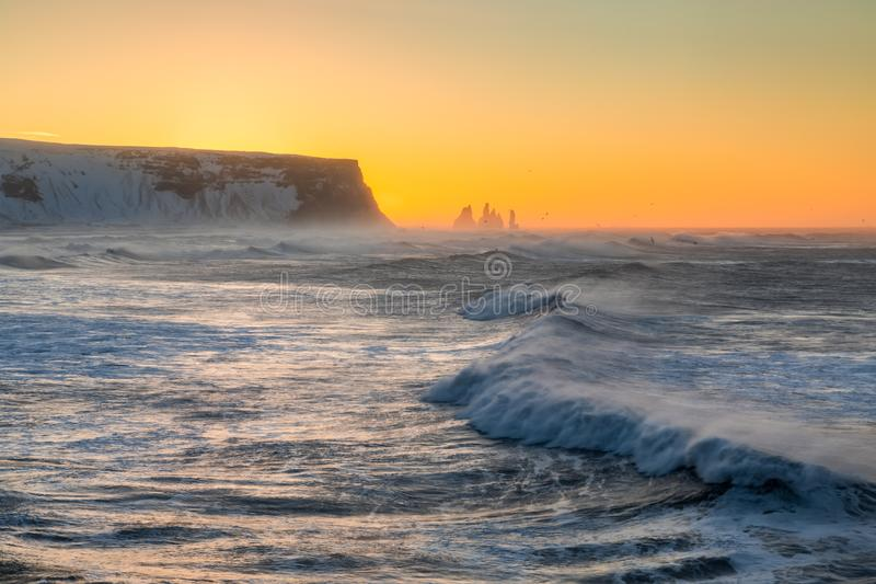 Sunrise at Cape Dyrholaey, the most southern point of Iceland. View from cape Dyrholaey on Reynisfjara Beach and Reynisdrangar basalt sea stacks, Iceland. Stormy royalty free stock photos