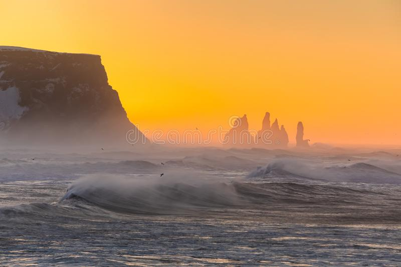 Sunrise at Cape Dyrholaey, the most southern point of Iceland. View from cape Dyrholaey on Reynisfjara Beach and Reynisdrangar basalt sea stacks, Iceland. Stormy royalty free stock photography