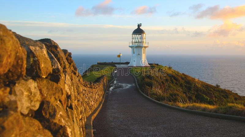 Sunrise at Cape Reinga lighthouse, North Island, Northland, New Zealand, Pacific ocean, Tasman sea. Cape Reinga Lighthouse is a lighthouse at Cape Reinga in the stock photography