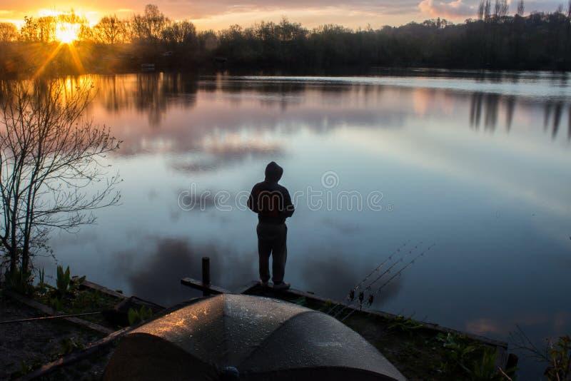 Sunrise Carp Angler overlooking Lake royalty free stock photography