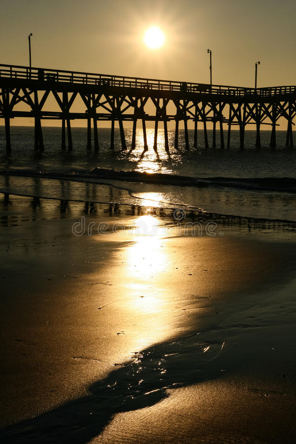 Sunrise Cherry Grove Pier Myrtle Beach Portrait. A beautiful golden sunrise over the famous landmark Cherry Grove ocean beach pier, reflecting off the water and stock photos
