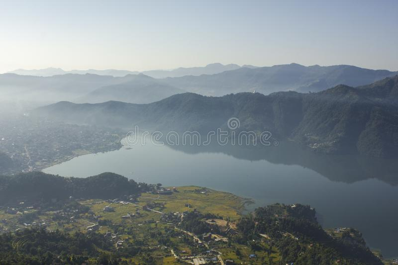 A sunrise in a cloudy and foggy green mountain valley with a lake and a city on the shore. Sunrise in a cloudy and foggy green mountain valley with a lake and a stock image