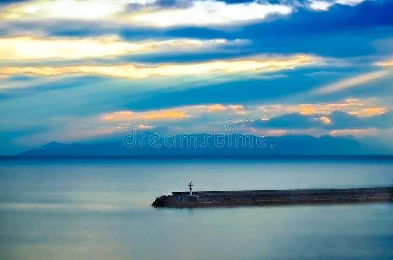 Sunrise in a cloudy sky.Pier in the morning mist at the marina Z stock photography