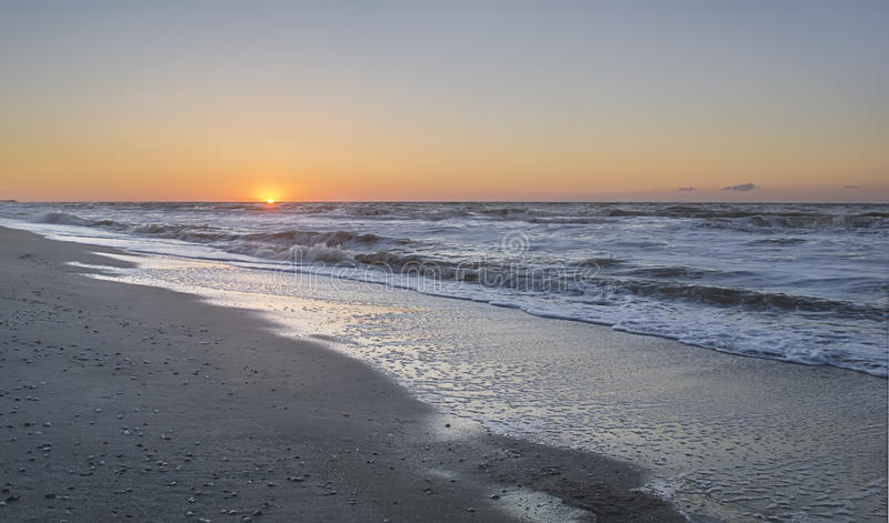 Sunrise on a cold beach sea. royalty free stock photos