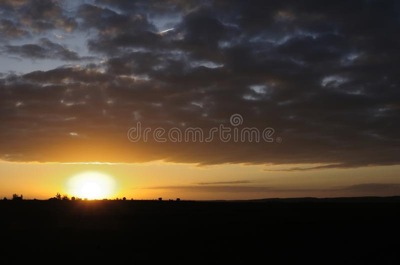 Sunrise in the countryside. A day dawns. The orange contrast of the sun with the darkness of dawn. It makes this landscape royalty free stock photo