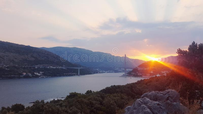 Sunrise in Croatia. Beautiful sunrise peaking through some mountains by the bridge and river royalty free stock photo