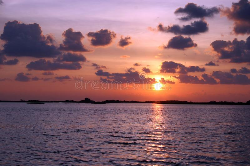 Sunrise WIth Dark Clouds and bright multi color. Sky.Picture taken on the water from a boat stock image