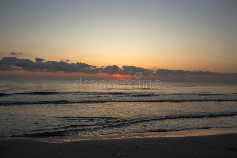 Sunrise. Dawn on the Mediterranean coast, Tunisia Sand in the foreground, small waves, the sun above the horizon, long clouds royalty free stock images