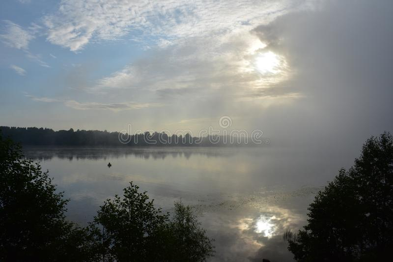 Sunrise dawn morning on the river boat, the sun is shining behind the clouds and fog stock photography