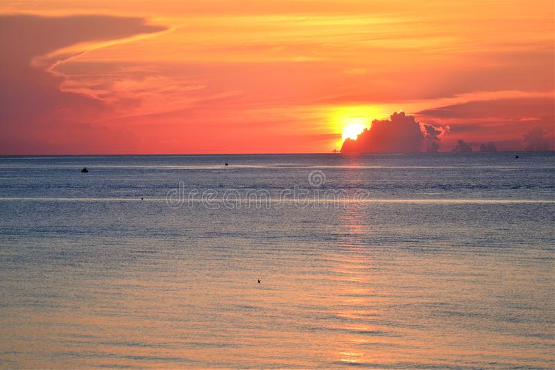 Sunrise is even more colorful with cloud cover filtering the rays stock image