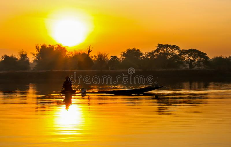 Sunrise fisherman and dinghy stock image