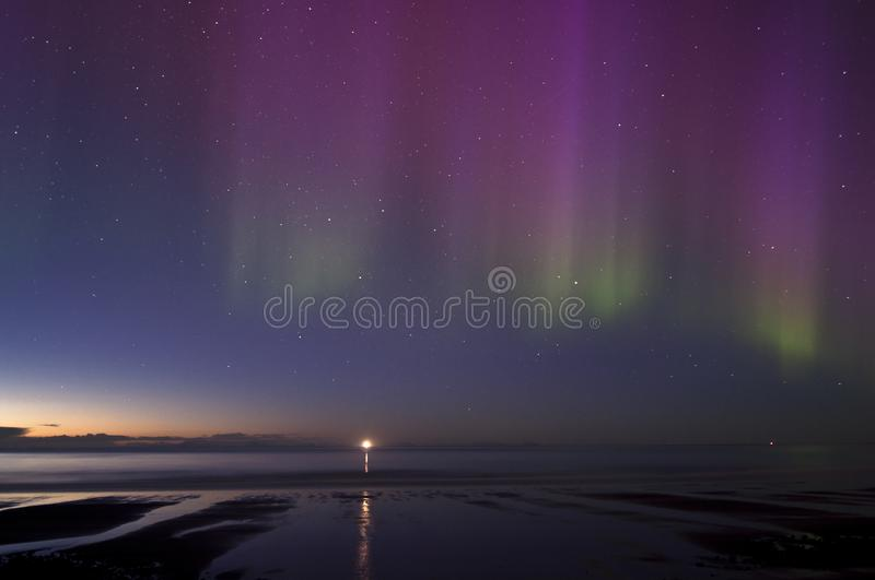 Sunrise and fishermen boats in the horizon and lighthouse in the distance under northern lights stock photo