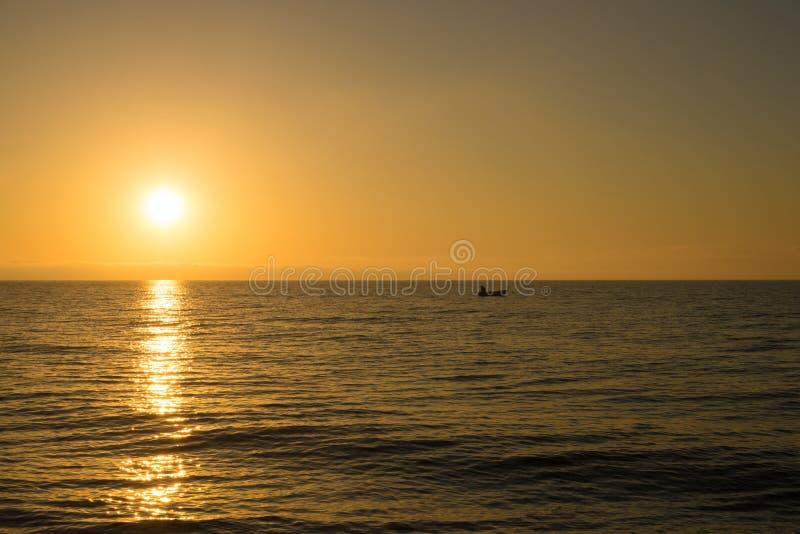 Sunrise with fishing boat stock photo