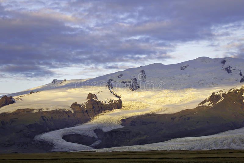 Sunrise on Fjalljokul glacier. Glacier under cloudy sky partially lit by early morning sun stock photos