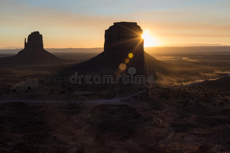 Sunrise flares behind the buttes in Monument Valley royalty free stock image
