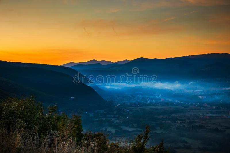 Sunrise with fog, mountains and town in the background. Drvar in Bosnia and Herzegovina stock image