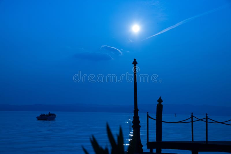 Sunrise on garda lake, Sirmione, Italy. Jetty with motorboat moored on Lake Garda at sunset, Sirmione, Lombardy, Italy, Europe royalty free stock image