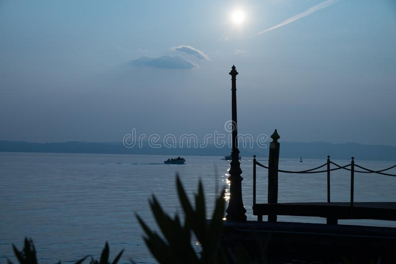 Sunrise on garda lake, Sirmione, Italy. Jetty with motorboat moored on Lake Garda at sunset, Sirmione, Lombardy, Italy, Europe stock photos