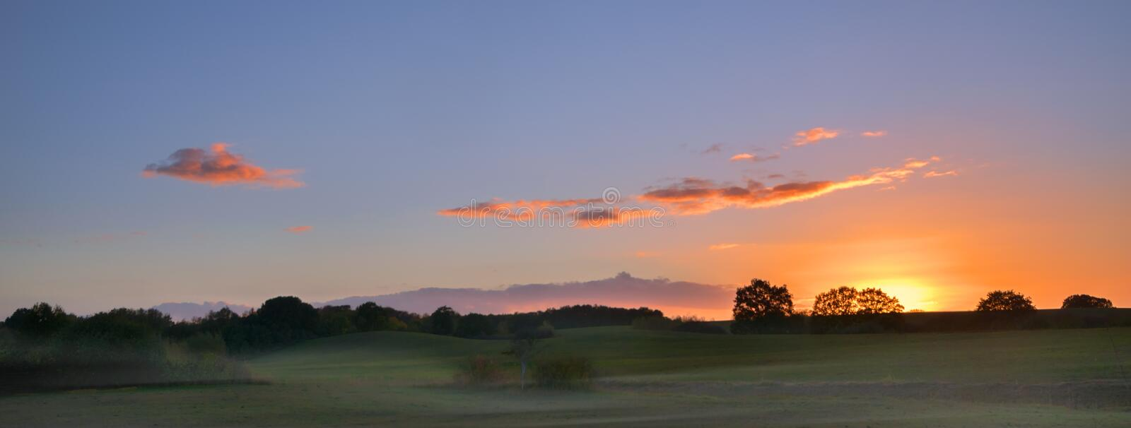 sunrise with glowing clouds over a wide rural landscape with meadows and trees in the morning mist, panorama format with copy spa stock images