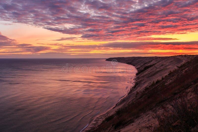 Sunrise at Grand Sable Dunes - Grand Marais, Michigan. A spectacular sunrise over Grand Sable Dunes near Grand Marais, Michigan. The Log Slide Overlook is part royalty free stock image