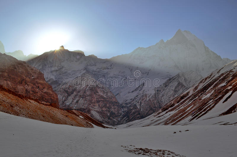Sunrise in the Himalayan mountains. Machapuchare peak, Fish tail top. Sunbeams. royalty free stock image