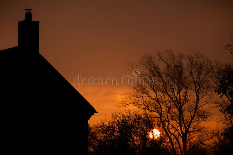 Sunrise at home. Early morning sun glowing through misty morning autumn trees. Relaxing rural landscape at dawn with an orange sun rising behind a silhouette stock images