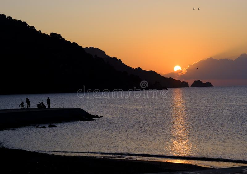 Sunrise with human sillhouettes royalty free stock photo