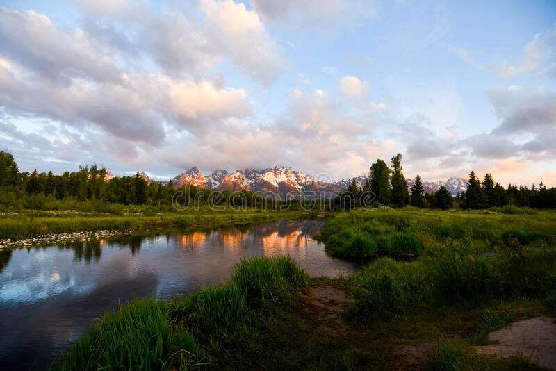 The sunrise is illuminating the snow covered peaks of the  Grand Teton mountain range, reflecting in the still water of. The early morning sun is illuminating royalty free stock images