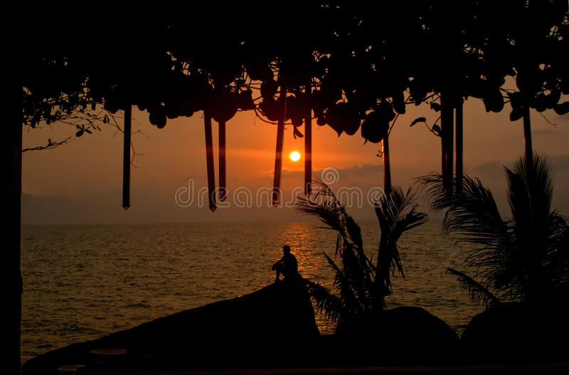 Sunrise in Koh Samui. Silhouette of a man sitting on the rocks overlooking the ocean in Koh Samui, Thailand stock images