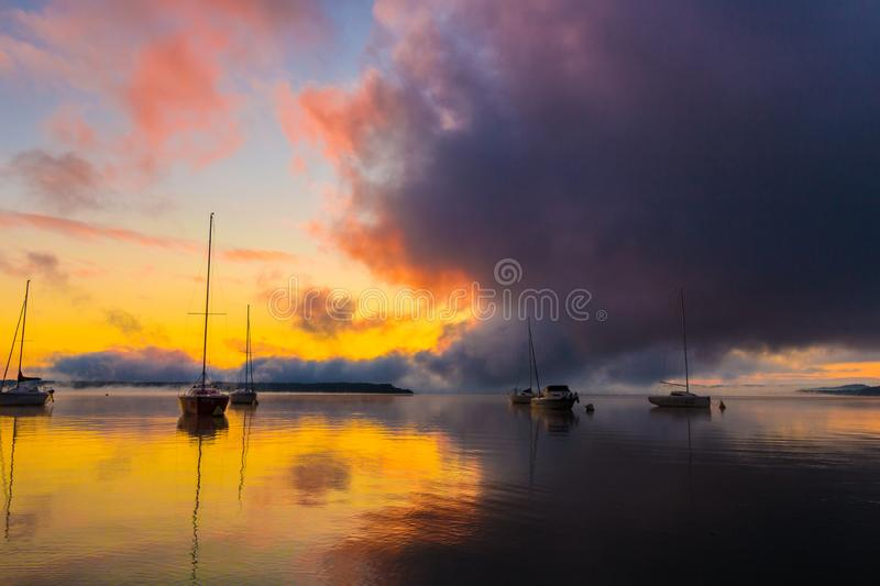 Sunrise on the lake with boats, reflection of sun in water, with fog and clouds on summer morning stock photography