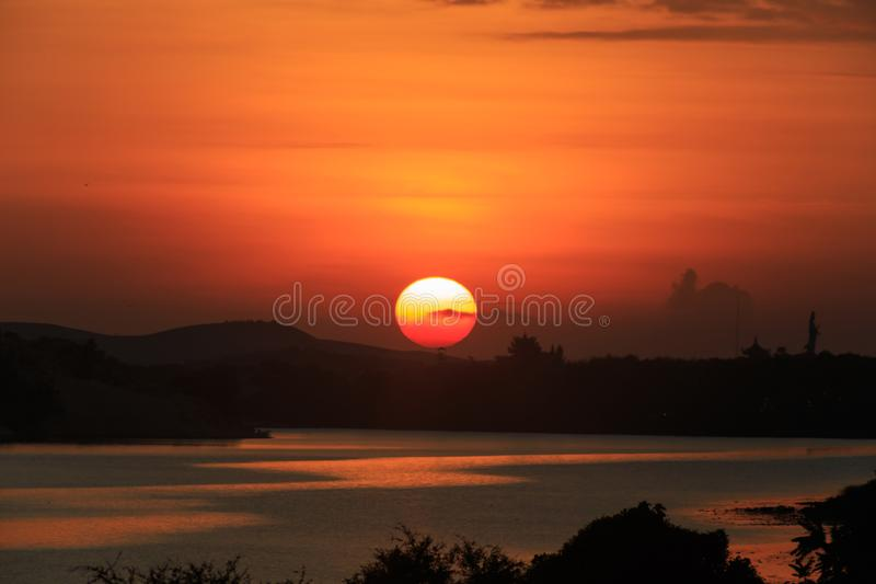 Sunrise on the lake. Early morning landscape. mist on the water, forest silhouettes and the rays of the rising sun stock images