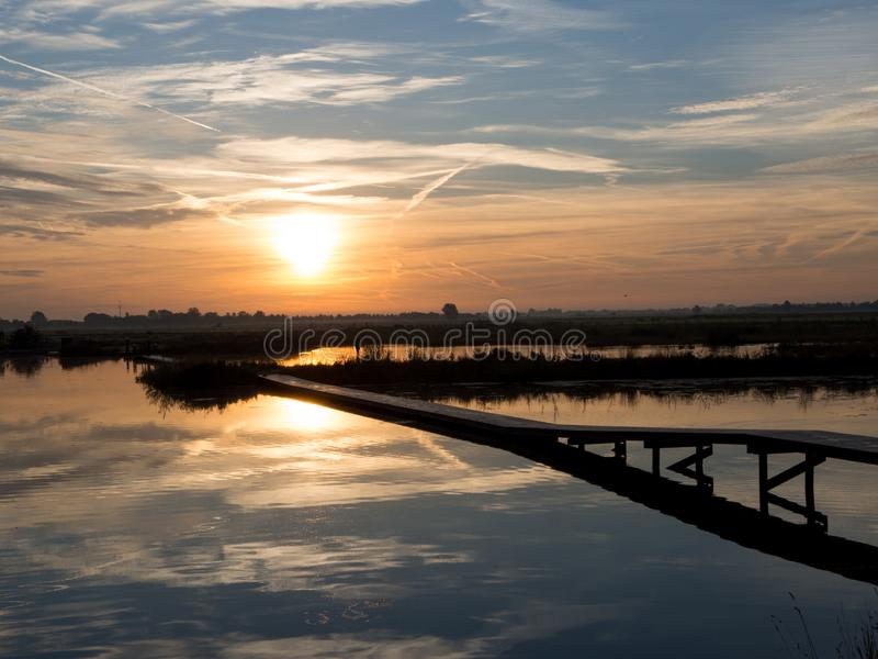 Sunrise on the lake. Polder Blokhoven Schalkwijk. The polder Blokhoven is a beautiful nature area in Schalkwijk, the Netherlands. Sunrise over the water is royalty free stock photo