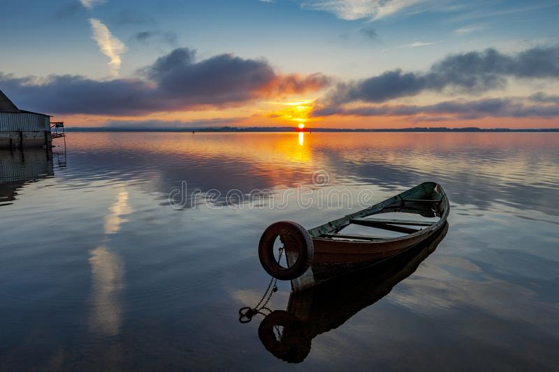 Sunrise on Lake Seliger with an old boat in the foreground. Sunrise on lake Seliger with an old fishing boat in the foreground, Ostashkov, Tver region, Russia royalty free stock photo
