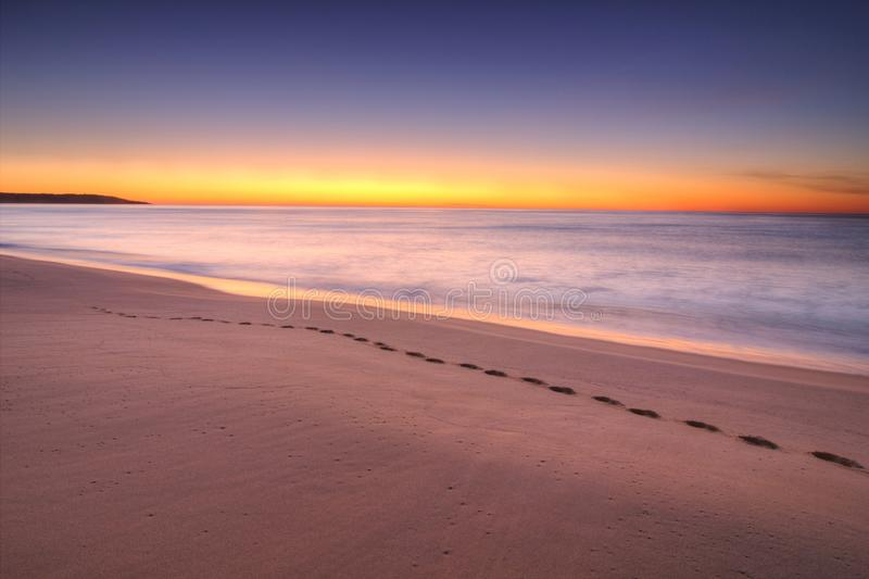 Sunrise at Lakes Entrance, Victoria, Australia. A view of the sun rising from the horizon over the coast of Lakes Entrance, Victoria, Australia, with footsteps royalty free stock photography