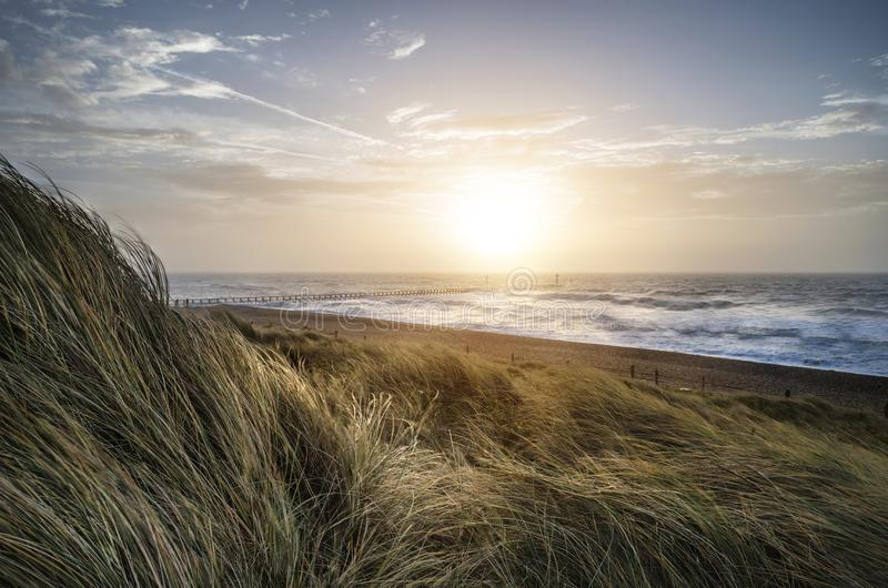 Beautiful sunrise landscape image of sand dunes system over beach with wooden boardwalk royalty free stock photography
