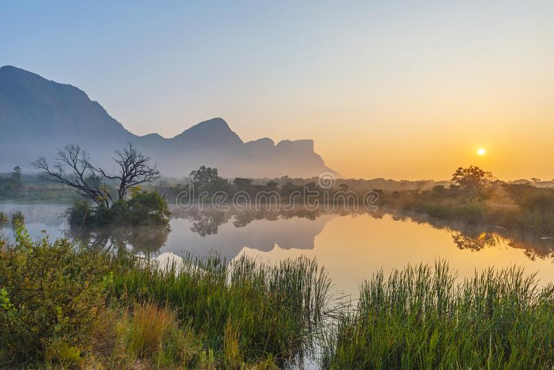 Savannah in Entaben at Sunrise, Limpopo, South Africa. Sunrise landscape inside the Entabeni Safari Game Reserve with the Hanglip or Hanging Lip mountain peak stock image