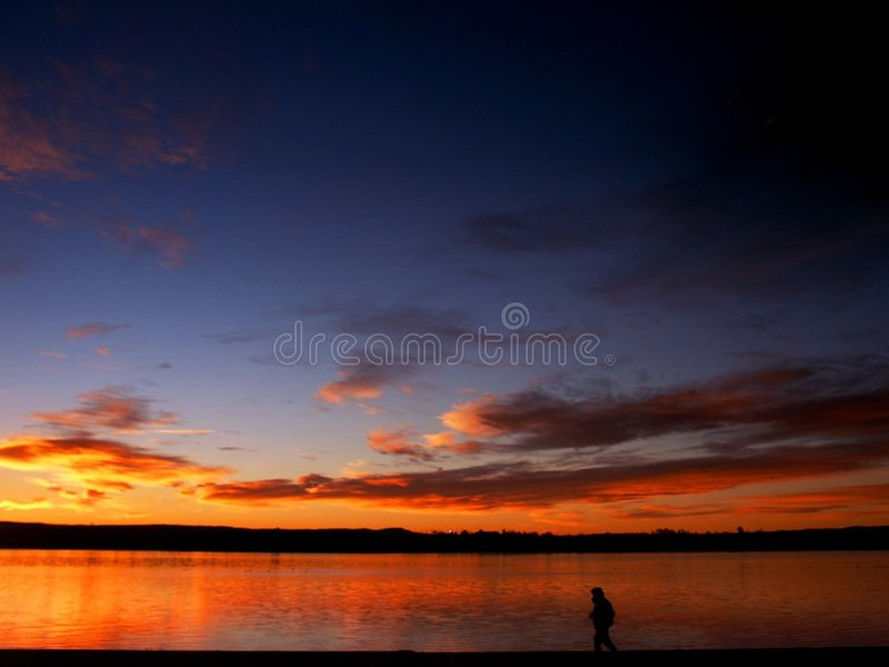 Sunrise landscape with person walking royalty free stock image