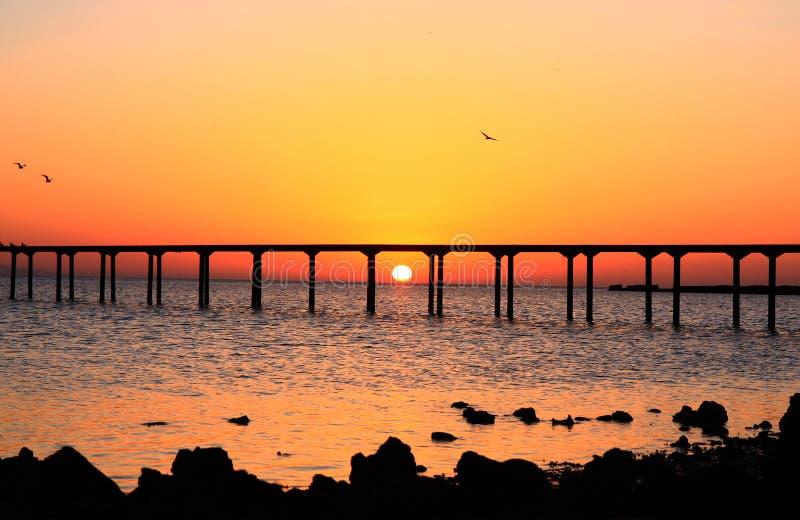 Sunrise landscape, sea with bridge and orange sky background, birds flying, sun on the horizon. Bright stock images